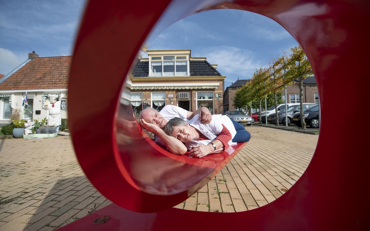 Johannes en Sjoerdtsje Huizenga op het kunstbankje voor hun bakkerswinkel. Links de plassende bakkerspop als fontein.