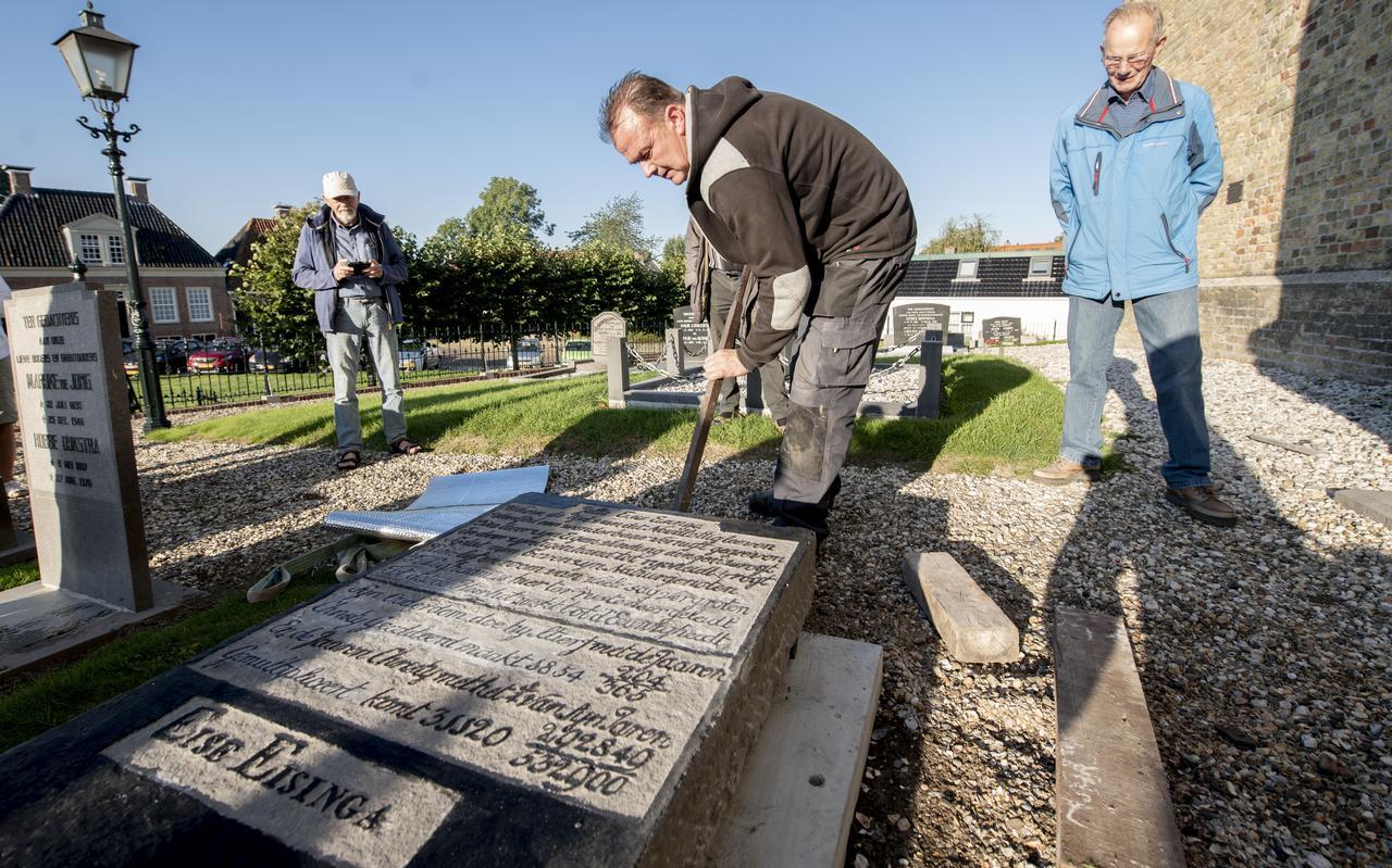 Ben Seldenrijk legt de gerestaureerde grafsteen van Eise Eisinga op zijn nieuwe 'bed', een betonnen plaat.