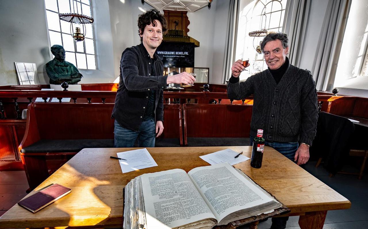Biograaf Johannes Keekstra en uitgever Louw Dijkstra (rechts) proosten onder toeziend oog van Piet Paaltjens' buste in het kerkje van het Friese Foudgum.