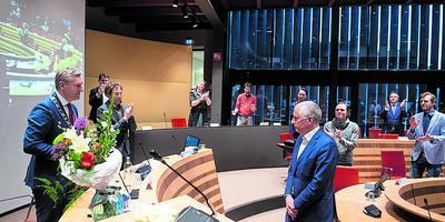 Bloemen van burgemeester Sybrand Buma voor de kersverse wethouder Bert Wassink.