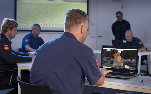 Brandweermannen gaan online een kasteelbrand te lijf, met behulp van Minecraft. Op de achtergrond staand Guido Swildens.
