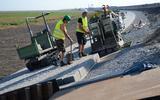Medewerkers van Heijmans leggen de betonnen zetstenen met een speciaal daarvoor gemaakte machine op de Lauwersmeerdijk.