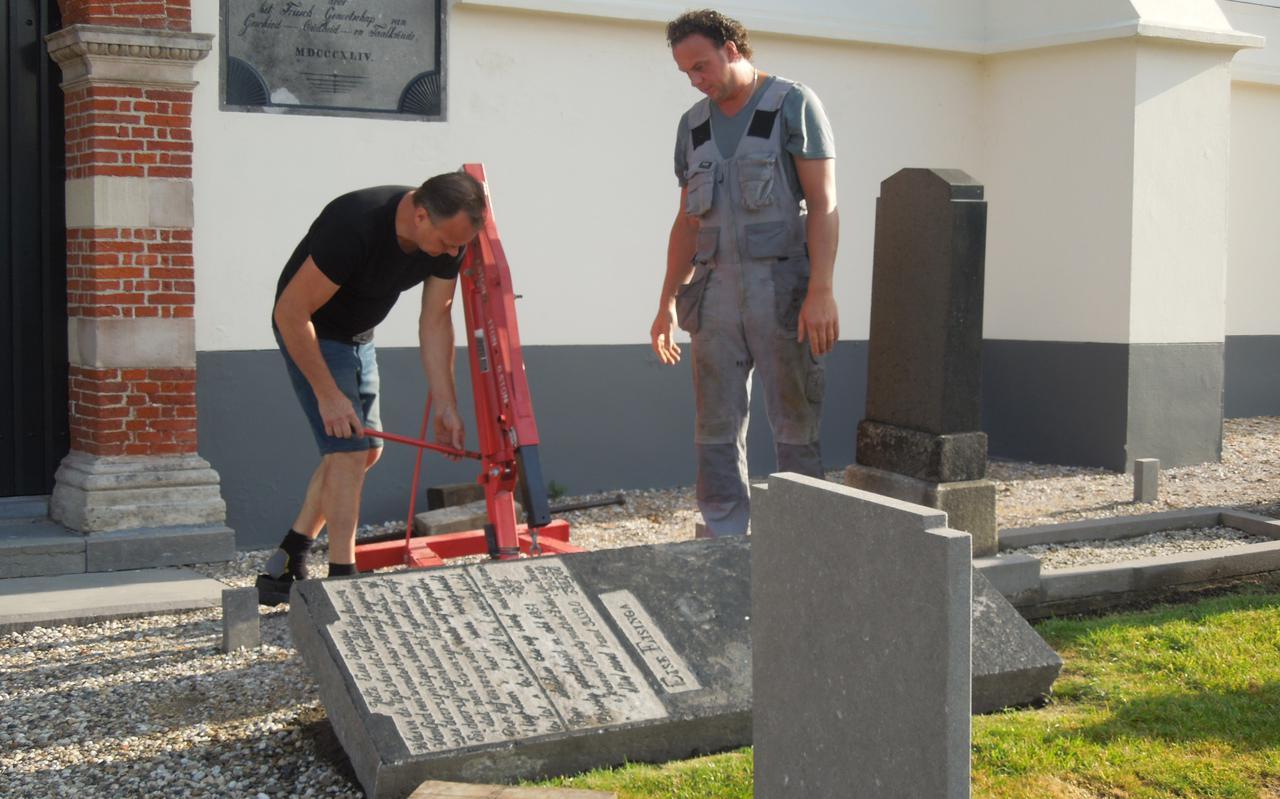 De grafsteen van Eise Eisinga, op het kerkhof bij d'Alde Wite in Dronryp, wordt gelicht voor restauratie. FOTO JOHAN DALSTRA