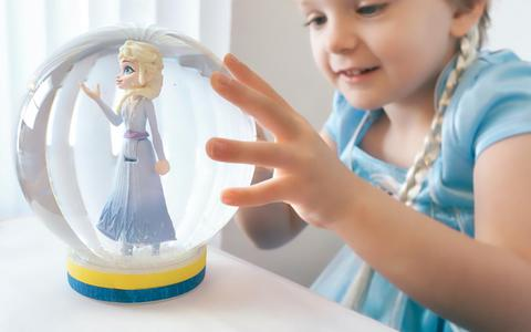 Phoenix, AZ / USA - October 10, 2020: Young girl dressed in Disney Frozen II dress and braid smiling with hands on snow globe that contains Elsa.