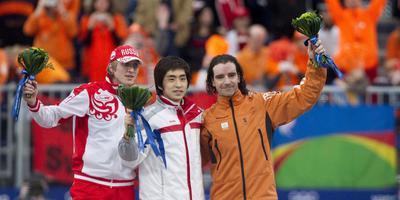 Seung-Hoon Lee is het stralende middelpunt in februari 2010, na de olympische 10 kilometer in Vancouver. Links de zilveren Ivan Skobrev, rechts de bronzen Bob de Jong. FOTO ANP ROBIN UTRECHT