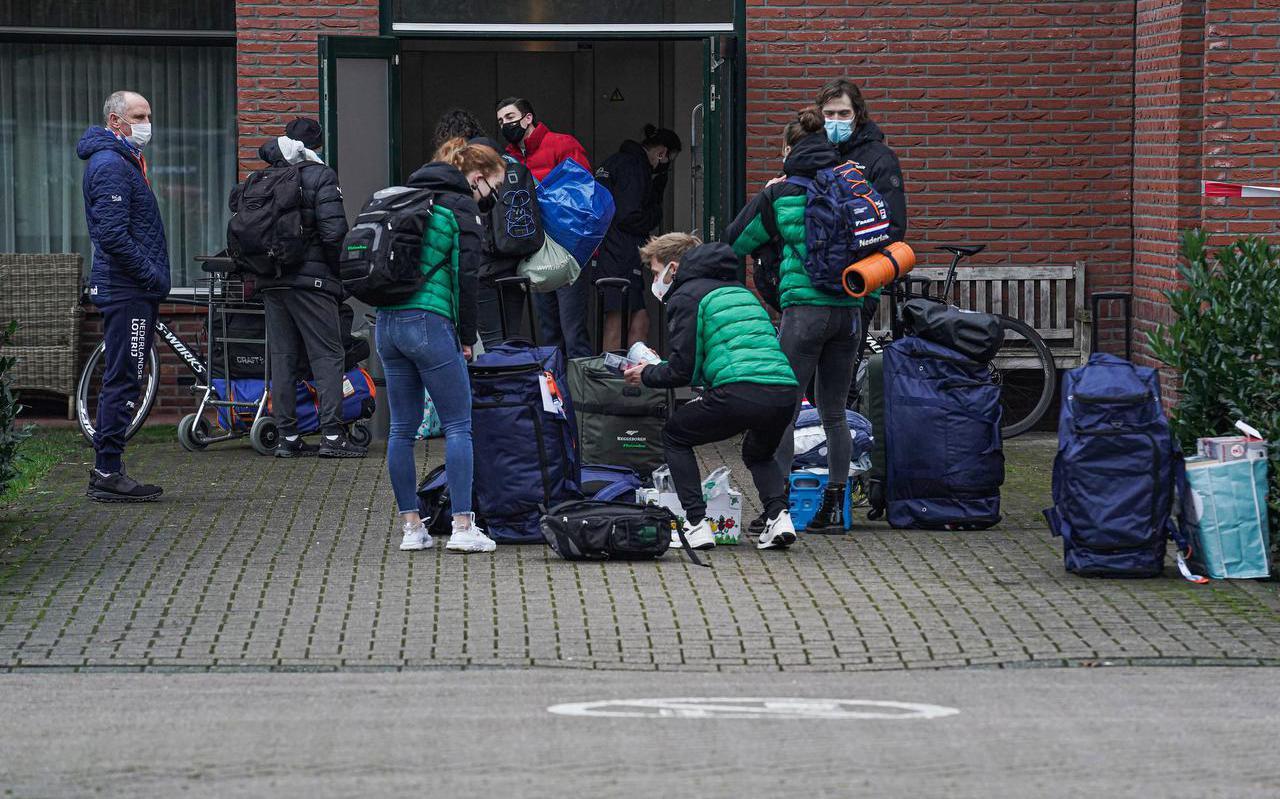 Schaatsers en coaches wachten voor de zijingang van het Van der Valk-hotel in Wolvega totdat ze de schaatsbubbel kunnen betreden.