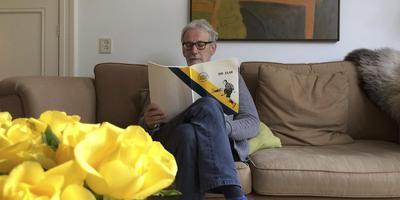 Willem van der Knoop, kleinzoon van Harry Waites, leest thuis in Leeuwarden in het jubileumboek van Frisia. FOTO LC.