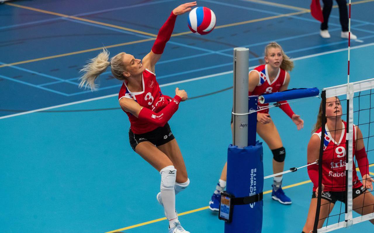Anlène van der Meer haalt uit namens VC Sneek. Rechts spelverdeelster Nienke Tromp, in het midden Britt Schreurs.
