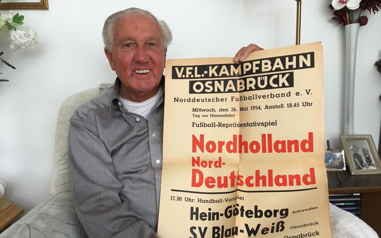 Hampie Bakker anno 2019. Trots toont hij de affiche die hij 65 jaar geleden na de semi-interland in Osnabruck wist te bemachtigen.