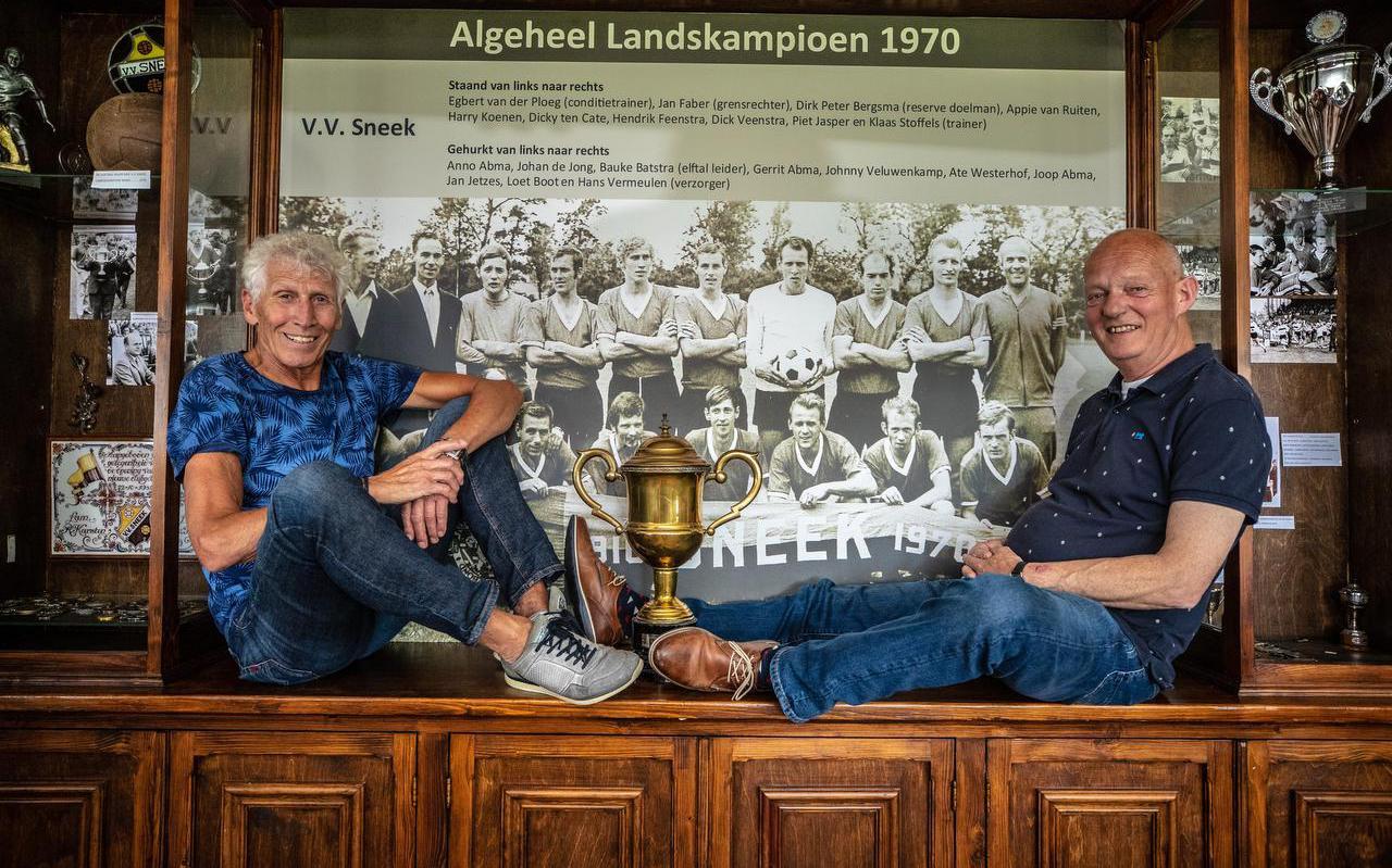 Harry Koenen (links) en Loet Boot 50 jaar na dato bij de grote kampioensfoto in het Sneek-clubhuis. Koenen staat vijfde van links, Boot zit gehurkt, uiterst rechts.