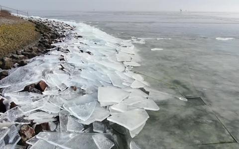 Kruiend ijs kruipt vanaf het IJsselmeer de Afsluitdijk op