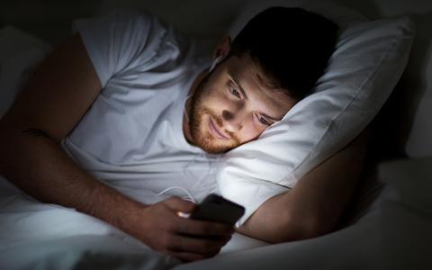 Man met mobiel in bed
